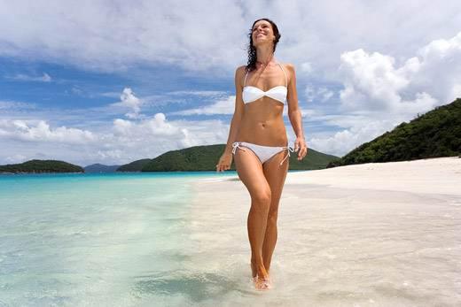 Девушка прогуливается по пляжу в белом купальнике