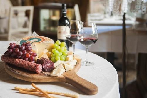 Красное вино разлитое в два фужера и мясные закуски с фруктами