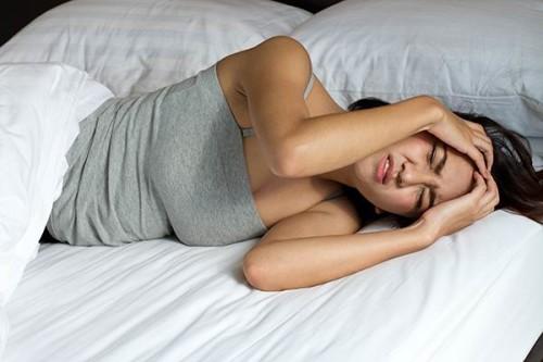 Девушка в постели держится за голову