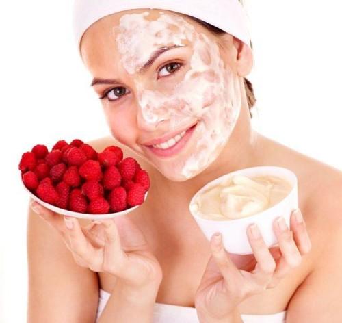 Девушка наносит маску на лицо из свежих ягод