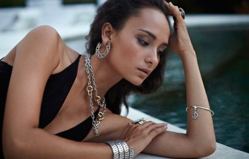 Красивая девушка в черном платье и в серебряных украшениях