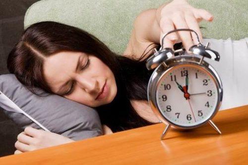 девушка просыпается от звука будильника