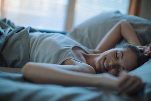 Спящая в постели молодая женщина