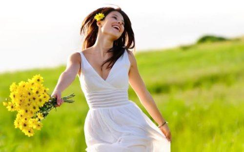 Счастливая женщина в поле с букетом цветов