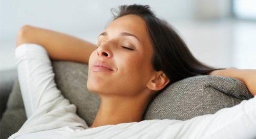 Молодая женщина сидит на диване